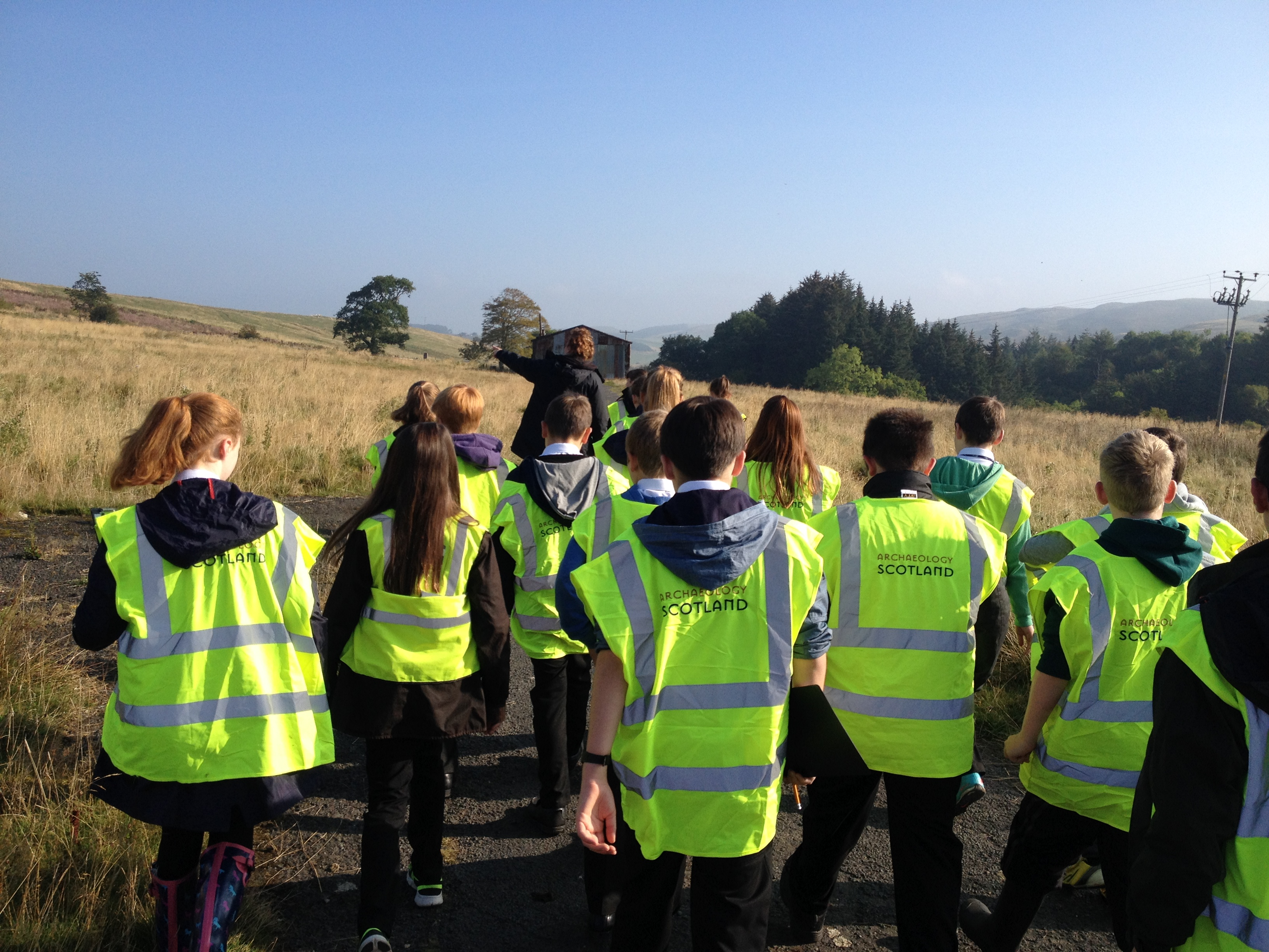 Claire Druett leads a class of young building surveyors towards the POW hut, in glorious weather.